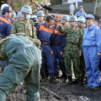 Surveying the damage: Prime Minister Shinzo Abe (right) inspects typhoon-wrecked areas on Tokyo's Izu-Oshima Island on Sunday | KYODO