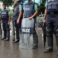 Confrontation: Bangladeshi policemen stand guard on a street on Friday after at least six people were killed and dozens injured when security officials clashed with opposition supporters trying to defy a ban on protests in Dhaka | AP