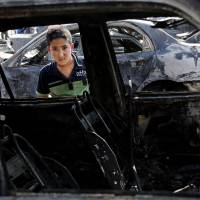 Stunned: A boy inspects a destroyed car after a car bomb attack hit the Sha'ab neighborhood of Baghdad on Sunday. Insurgents unleashed a new wave of car bombs in Shiite neighborhoods of Baghdad, killing and wounding dozens of people, officials said | AP