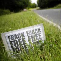 Drilling it in: An anti-fracking protest sign stands on the side of a road leading to Cuadrilla Resources Ltd.'s exploratory shale gas drilling site in Balcombe, England, in July. | BLOOMBERG