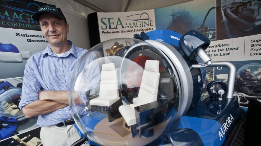Deep blue: Seamagine Hydrospace Corp. co-founder Charles Kohnen poses for a photo beside a model of a submarine during the Monaco  Yacht Show in September.