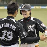 Yuki Karakawa greets fellow Lotte Marine Daichi Suzuki after the shortstop scored a rare home run in the fifth inning.  | KYODO