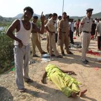 An Indian man gestures alongside the body of a Hindu devotee crushed in a stampede outside the Ratangarh Temple at Datia district in central Madhya Pradesh state on Sunday. | AFP