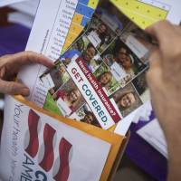 Information distribution: A volunteer for the Get Covered America campaign organizes materials before canvassing the neighborhood to inform prospective health insurance consumers about new insurance possibilities available through the Affordable Care Act, in Englewood, New Jersey, on July 27. | BLOOMBERG