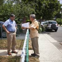 One on one: Claude Cesard (right), a volunteer with the Get Covered America campaign, talks with Leonardo Acosta, who has insurance, about health insurance possibilities through the Affordable Care Act in Englewood, New Jersey, on July 27. | BLOOMBERG