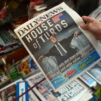 Douche: A woman buys a copy of the New York Daily News featuring a photo of U.S. House Speaker John Boehner on Tuesday, following a shutdown of the federal government. | AFP-JIJI