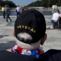 Temporary victory: World War II Veteran George Bloss, from Gulfport, Mississippi, looks out over the National World War II Memorial in Washington on Tuesday. Veterans who had traveled from across the country were allowed to visit the memorial after it had been officially closed because of the partial government shutdown. After their visit, National World War II Memorial was closed again. | AP
