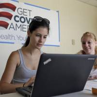 Roll up, sign up: A woman receives help signing up for the Affordable Care Act from a volunteer with Enroll America, a private nonprofit organization running a grass-roots campaign to encourage people to sign up for health care, in Tampa, Florida, on Tuesday. | AP
