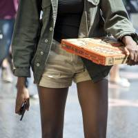 Mind the gap: A young woman carrying a pizza and a phone walks down the fashionable Hollywood Boulevard in Hollywood, California, on Sept. 17. | AFP-JIJI