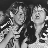 Mixed emotions: Two girls watch the Beatles perform in Philadelphia on Aug. 16, 1966. Barricades manned by policemen were erected about 50 meters from the stage in an effort to keep the band's young fans from rushing the 'Fab Four.' | AP