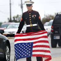 Signaling his displeasure: A U.S. Marine veteran shows his concern over the government shutdown by holding an American flag upside down, a signal of distress, in Beech Grove, Indiana, on Tuesday. | AP