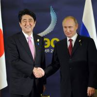On message: Prime Minister Shinzo Abe meets Russian President Vladimir Putin on the sidelines of the Asia-Pacific Economic Cooperation forum in Bali, Indonesia, on Monday. | AP