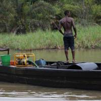 Black gold: Suspected thieves pilot a boat loaded with a cargo of stolen crude oil in Bayelsa, Nigeria. According to one oil trader: 'All the authorities are involved — the oil companies, the military, the politicians. There's plenty of money to be made.' | AP