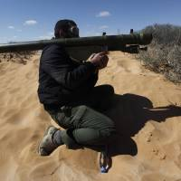 In the wrong hands: A Libyan rebel aims an SA-7 shoulder-fired anti-aircraft missile launcher in the oil town of Ras Lanouf in March 2011. A new independent report warns the Syrian government's arsenal of 20,000 portable anti-aircraft missiles are at risk of falling into the hands of terrorist groups. | AP