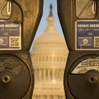 In need of a quick fix: A pair of parking meters partly obscure the U.S. Congress in Washington on Monday as the federal government shutdown crisis dragged into a third week. | AFP-JIJI