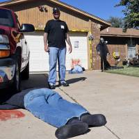 No offense: Johnnie Mullins shows a Halloween dummy lying under a truck with blood splattered on the driveway. | AP