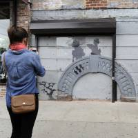 Arch comment: A woman (left) looks at work by British graffiti artist Banksy as Feliciano Perez guards on Saturday in the Brooklyn borough of New York. The building owner has hired security guards and installed a metal gate to protect a work by Banksy. Cara Tabachnick, whose family owns the building, said the goal is to preserve the artwork 'so it can be viewed and enjoyed.' | AP