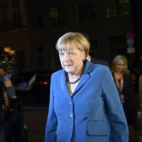 Right-hand woman: German Chancellor Angela Merkel arrives at a TV studio in Berlin with her office manager, Beate Baumann (right), on Sept. 22 for a talk show after the general elections. | AFP-JIJI