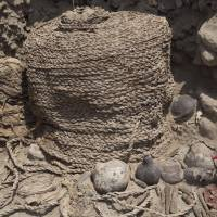 Rare and intact: Archaeologists clean around one of the mummy bundles unearthed at a Wari tomb in Lima on Thursday. | AP