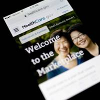 Teething troubles: The Healthcare.gov website is displayed on a phone in Washington on Thursday. | BLOOMBERG