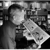 A laugh at work: Charles M. Schulz reads over a 'Peanuts' strip in an undated photograph by Tom Vano. | © 2013 PEANUTS WORLDWIDE LLC
