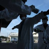 Next nightmare: A worker is screened for radiation in Minamisoma after leaving the 20-km exclusion zone around the wrecked Fukushima No. 1 nuclear power plant in September 2011. | BLOOMBERG