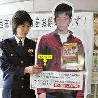 A police woman unveils a life-sized poster of Ichihashi on the second anniversary of Hawker's murder. | KYODO