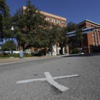Crime scene: An X marks the spot on Elm Street where the fatal bullet struck U.S. President John F. Kennedy on Nov. 22, 1963, near the former Texas School Book Depository in Dallas. | AP