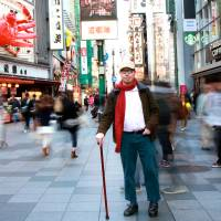 Obstacle course: Michael Gillan Peckitt stands on the main Dotonbori drag in Osaka. 'For the foreigner with a physical disability, the need to negotiate the environment safely is of paramount importance,' he writes. | DANNY GONG