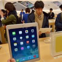 Must-have: Customers look over Apple's new iPad Air tablets at an Apple store in Tokyo on Friday. More than 300 customers lined up to buy the slimmed-down device, which debuted worldwide. | AFP-JIJI