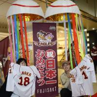 Stoked: Fans of the Tohoku Rakuten Golden Eagles hold up their favorite players' jerseys in front of the Fujisaki department store in the city of Sendai on Monday before a special sale to celebrate the team's first Japan Series championship. | KYODO