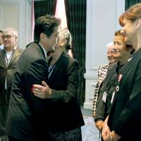 Prime minister's prerogative: Prime Minister Shinzo Abe, during a visit to Turkey last month, hugs a relative of Orhan Suyolcu, a deceased former Turkish Airlines captain who, in 1985, flew in to Tehran during the Iran-Iraq War to retrieve 215 stranded Japanese. | KYODO