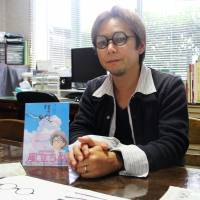 Far-sighted: Yasuyuki Kobayashi wears glasses he designed based on those worn by the main character in Hayao Miyazaki's animated film 'Kaze Tachinu' ('The Wind Rises'). | KYODO