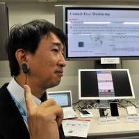 Driving aids: Yasuhiko Nakano, a research manager of Media Processing Systems Laboratories at Fujitsu Laboratories Ltd., shows a drowsiness detection sensor. | YOSHIAKI MIURA