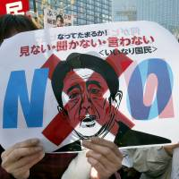 Outcry: A demonstrator holds a poster of Prime Minister Shinzo Abe that reads 'Don't see, don't listen, don't speak' while protesting against the state secrecy bill in front of the Diet in Tokyo on Tuesday. | AP