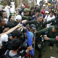 Working class passengers: Typhoon survivors jostle for a chance to board a C-130 military transport plane Tuesday in the central Philippine city of Tacloban. Thousands swarmed the airport Tuesday seeking a flight out, but only a few hundred made it   AP