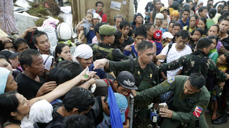 Working class passengers: Typhoon survivors jostle for a chance to board a C-130 military transport plane Tuesday in the central Philippine city of Tacloban. Thousands swarmed the airport Tuesday seeking a flight out, but only a few hundred made it
