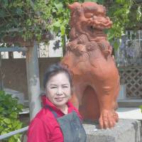 Proudly protective: Setsuko Oshiro stands infront of the 100-kg <B><I>sh</I><I>i</I><I>¯</I><I>s</I><I>a</I><I>¯</I></B> <B> that sits outside her studio in Ihara, Okinawa</B>. | STEPHEN MANSFIELD