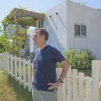 The island life: Keith Gordon stands outside his home in Kunigami in northern Okinawa.  The grounds are spacious enough to accommodate a kitchen garden, home music studio and patio area. | STEPHEN MANSFIELD