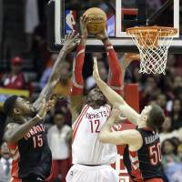 Double the challenge: Rockets center Dwight Howard puts up a shot between Raptors teammates Amir Johnson (left) and Tyler Hansbrough in first-half action on Monday in Houston | AP