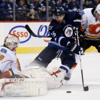 Sitting save: Calgary's Reto Berra stops a shot from Winnipeg's Blake Wheeler as teammate Lee Stempniak defends in the second period on Monday night. The Flames won 5-4 in a shootout. | AP