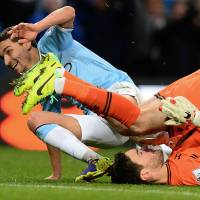 Put your back into it: Manchester City's Jesus Navas (left) celebrates his goal against Tottenham, to the dismay of Spurs 'keeper Hugo Lloris (right) on Sunday. City won 6-0. | AFP-JIJI
