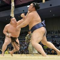 All in a day's work: Yokozuna Hakuho (left) defeats maegashira Tochinowaka for career victory No. 702 on Tuesday at the Kyushu Grand Sumo Tournament in Fukuoka. | KYODO