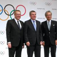 First visit as boss: IOC president Thomas Bach (center) stands with JOC president Tsunekazu Takeda and IOC vice president John Coates at a news conference in Tokyo on Wednesday. | KAZ NAGATSUKA