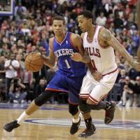 Shoulder to shoulder: Philadelphia's Michael Carter-Williams (left) moves the ball as Chicago's Derrick Rose defends during the Sixers' 107-104 win on Saturday | AP