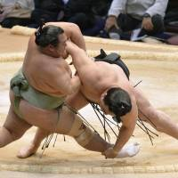 Skills and experience: Yokozuna Harumafuji (left) outworks Toyonoshima to win their match at the Kyushu Grand Sumo Tournament on Wednesday in Fukuoka | KYODO