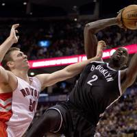 Tough angle: Brooklyn's Kevin Garnett puts up an off-balance shot against Toronto's Tyler Hansbrough in the second half on Tuesday. | AP