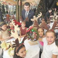 Christmas spirit: Children from Nishimachi International School in Tokyo wearing reindeer antlers show off a Christmas wreath they made Thursday at the Grand Hyatt Tokyo in Minato Ward as the hotel's general manager, Christophe Lorvo, looks on. | YOSHIAKI MIURA