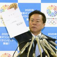 Papered over: Embattled Tokyo Gov. Naoki Inose holds up what he claims is a document that confirms he borrowed ¥50 million from the Tokushukai hospital group during a news conference at his office Tuesday. | KYODO