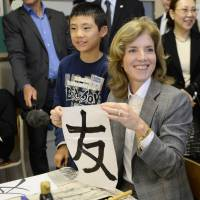 Art of diplomacy: Caroline Kennedy, the new U.S. ambassador to Japan, holds up the kanji for 'friend,' which she wrote in a calligraphy class during a visit to Mangokuura Elementary School in Ishinomaki, Miyagi Prefecture, on Monday. | AFP-JIJI